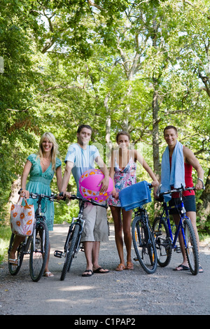 Four young people with bicycles standing on rural road - Stock Photo