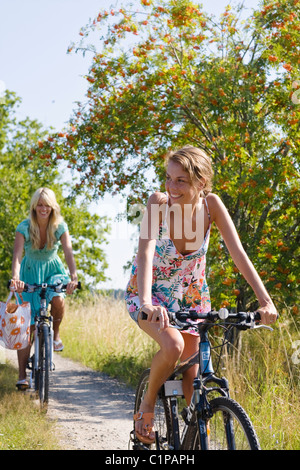 Two young women cycling - Stock Photo