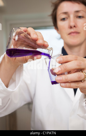 Scientist pouring liquid from beaker - Stock Photo