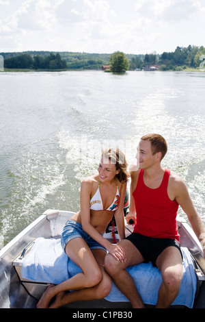 Young couple in motorboat on lake - Stock Photo