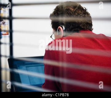 Man working in office, view from behind window blinds - Stock Photo