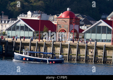 Scotland, Argyll, Oban, boat moored in harbour lined with buildings - Stock Photo