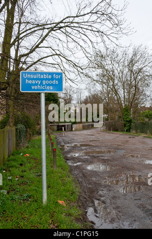 A sign reading 'Unsuitable for heavy goods vehicles' in front of a muddy, unmade road - Stock Photo