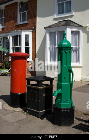 England, Essex, Thaxted, red letterbos, black litter bin, and green water pump - Stock Photo