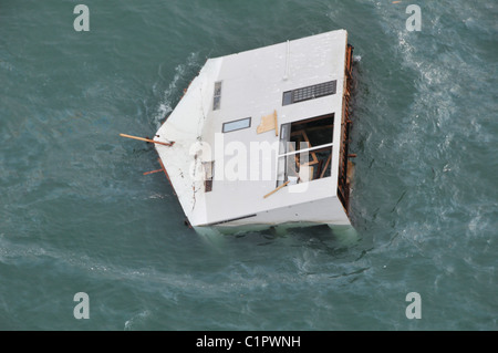 Aerial photo taken March 14 2011 of a house floating at sea near Sendai, Japan, in the aftermath of the earthquake - Stock Photo