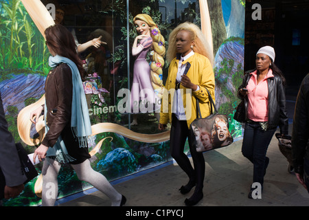 Disney character Rapunzel from their film Tangled stands looking at women, exemplifying feminine beauty. - Stock Photo