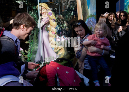 Disney character Rapunzel from their film Tangled stands looking at family, exemplifying feminine beauty. - Stock Photo