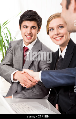 Photo of successful business partners handshaking after striking great deal with smiling woman near by - Stock Photo