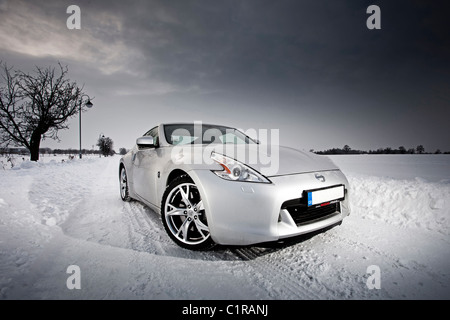 Silver sports car parked on a snow covered road - Stock Photo