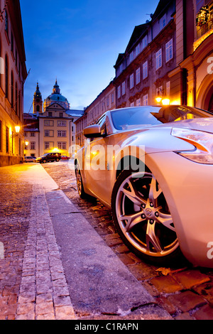 Silver sports car parked in the narrow ancient street - Stock Photo