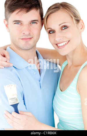 Portrait of a cheerful young couple holding a paint brush against white background - Stock Photo