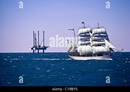 'Elissa', a three masted sailing tall ship, sailing near offshore oil rig platform in Galveston Bay, Galveston, - Stock Photo