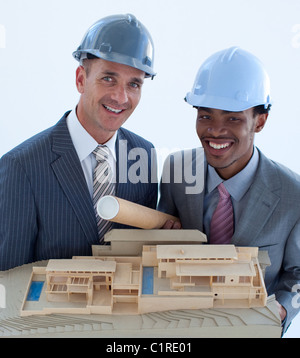 Smiling engineers with hard hats holding a model house - Stock Photo