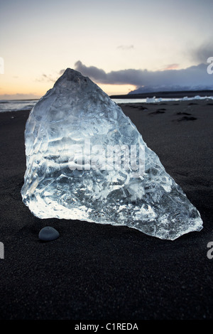 Icebergs on black beach with the tide washing around them in Iceland - Stock Photo