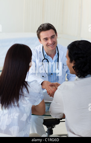 Smiling doctor explaining diagnosis to a couple - Stock Photo