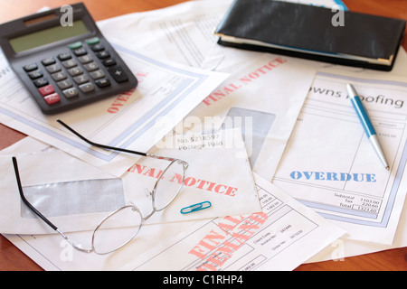 'Overdue Unpaid Bills on Table with Calculator and Cheque Book ' - Stock Photo