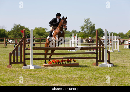 Woman riding horse at show jumping competition. - Stock Photo