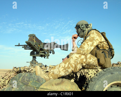 A gunner operates a 7.62mm general purpose machine gun atop a British Army WMIK Land Rover in Iraq. - Stock Photo