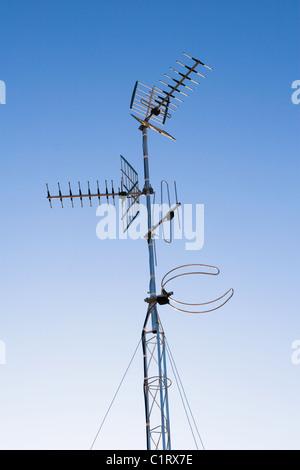 Tv antenna against blue sky - Stock Photo