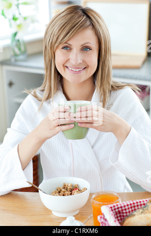 Beautiful woman holding a cup of coffee eating cereals in the kitchen - Stock Photo