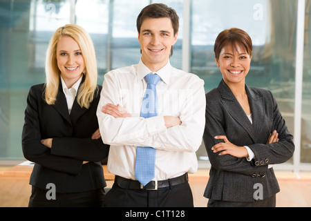 Image of cheerful colleagues keeping their arms crossed and looking at camera with smiles - Stock Photo