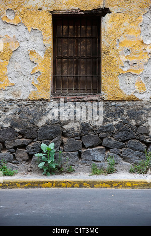 Barred window on dilapidated building exterior - Stock Photo