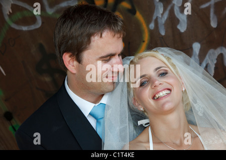 bridal couple in front of graffiti wall - Stock Photo