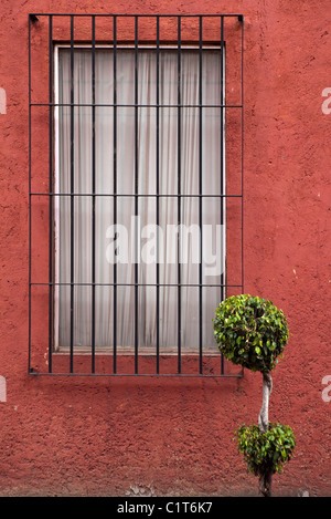 Barred window on stucco wall - Stock Photo