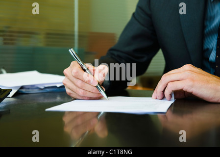 Executive signing paperwork, cropped - Stock Photo