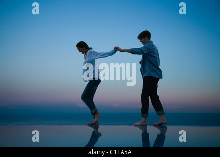 Couple walking together along edge of infinity pool, holding hands - Stock Photo