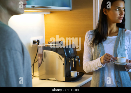 Woman enjoying cup of coffee in kitchen - Stock Photo