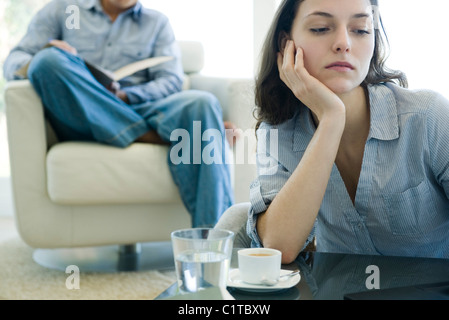 Woman leaning on elbow looking sad, man reading on sofa in background - Stock Photo