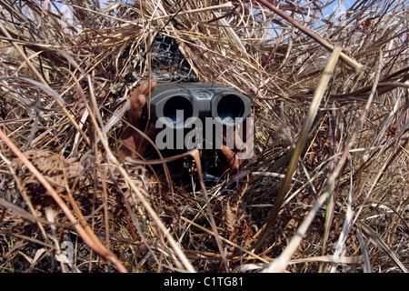 A scout observer practices observation techniques using a homemade ghillie suit. - Stock Photo