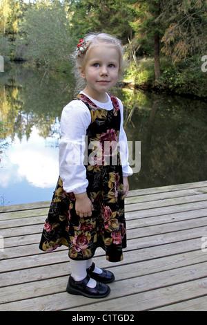 Three Year Old Well Dressed Caucasian Kid Girl Standing on Boardwalk - Stock Photo