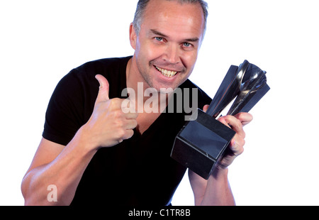 Middle aged man holding winning trophy and giving the thumbs up after beating his rivals in a golf competition - Stock Photo