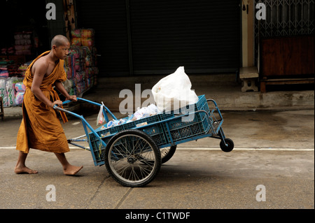 young novice on his morning alms round , mae sot town , northern thailand - Stock Photo