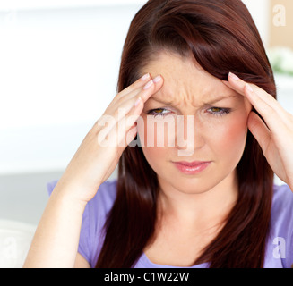 Dejected woman having a headache sitting in the living-room - Stock Photo