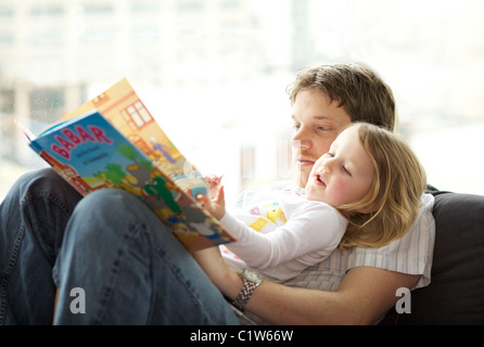 Caucasian father reading Babar the Elephant children book to his three year old daughter - Stock Photo
