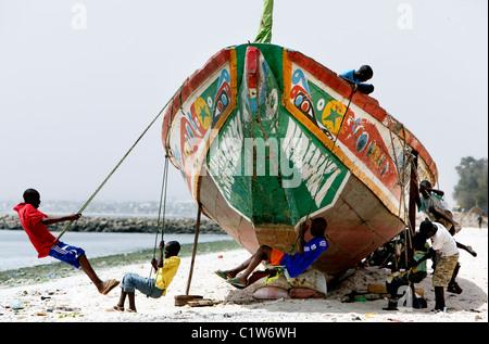 boys swinging on a fishing boat at a beach of Dakar, Senegal - Stock Photo