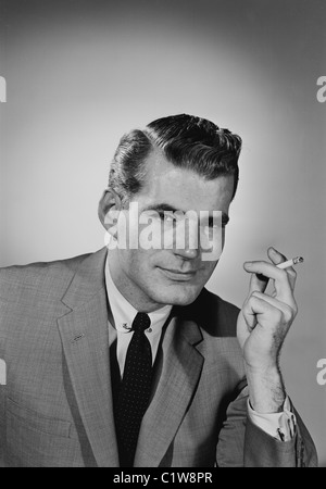Portrait of young man smoking cigarette - Stock Photo