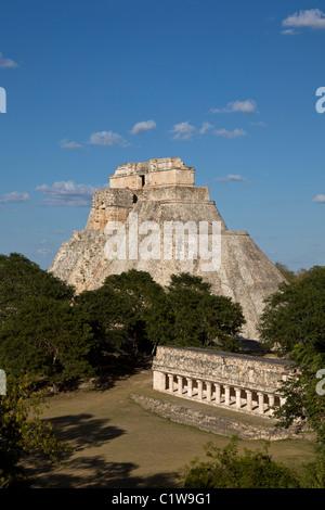 The Pyramid of the Magician (Pirámide del Adivino) rises over jungle in the Maya City of Uxmal, Yucatan Peninsula, - Stock Photo