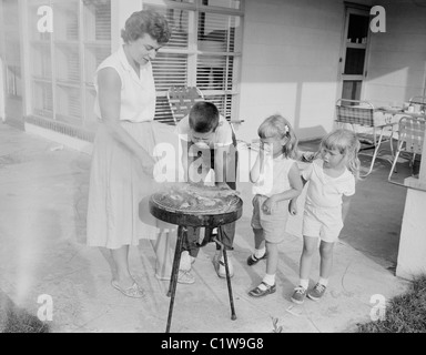 Mother doing barbecue and children watching her - Stock Photo