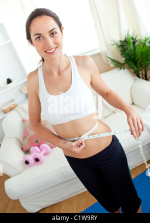 Pretty young woman measuring her waist with a tape in her living-room - Stock Photo