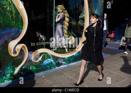 A Disney character Rapunzel from their film Tangled stands looking at women, exemplifying feminine beauty. - Stock Photo
