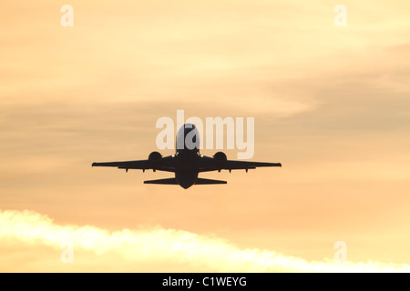 Silhouette of commercial aircraft during takeoff at sunset - Stock Photo