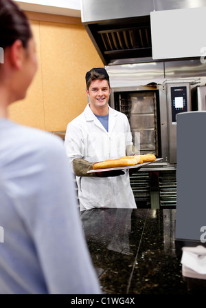 Cheerful baker showing his baguettes to a female customer in his shop - Stock Photo