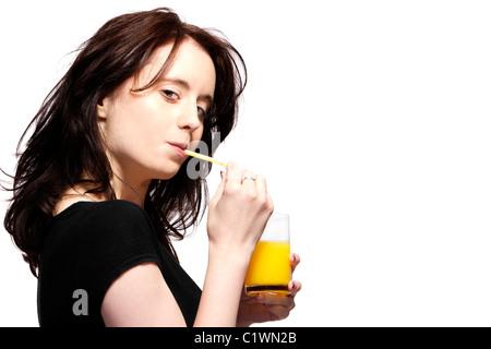 young woman in black shirt drinking orange juice - Stock Photo