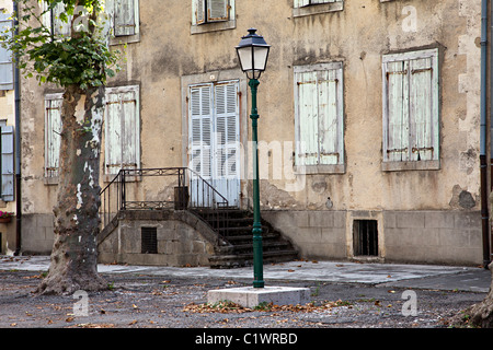 Faded shutters over windows and old street light Mas d'Azil department Ariege France - Stock Photo