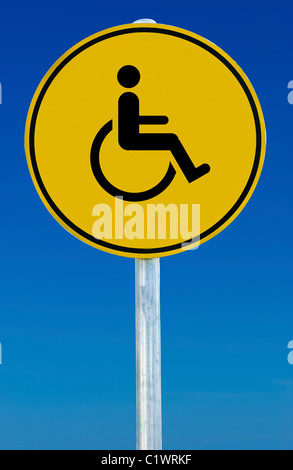 Wheelchair picture on a yellow sign isolated on a blue graduated sky. - Stock Photo