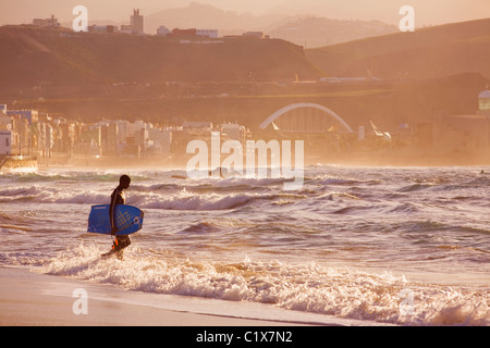 Bodyboarder heading out in the evening on Las Canteras Beach in Gran Canaria. - Stock Photo